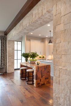 David James Custom Builders - Limestone doorway opens to an amazing kitchen features Goodman Hanging lamps illuminating paneled island topped with gray countertops framing sink placed in front of a secondary island made of reclaimed wood lined with iron swivel barstools with upholstered seats.