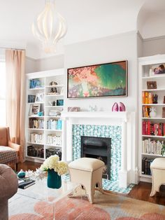 A Victorian house gets an interior update by way of this stylish living room. A blue-and-white fireplace surround adds color, built-ins provide storage and display space, and an eye-catching onion pendant light from Design Within Reach serves as a focal point. The colors in this space make it vibrant and interesting.