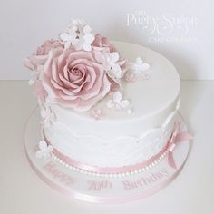 Vintage style 70th birthday cake in pink and white with lace and sugar roses