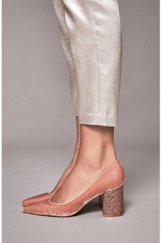 Allover glitter highlights the bold block heel of an event-ready pump in a sophisticated pointy-toe silhouette.