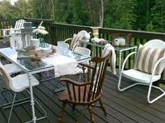 Already set for a big dinner, this large back porch houses a mixture of seating: vintage metal chairs, white plastic chairs, a canvas directors chair, an old wooden Windsor-style chair and a pair of Adirondack chairs. Designer Tip: You don't have to buy a set of all matching furniture. Mix it up and take the indoors out
