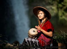 A woman playing drums at a waterfall in a remote region near Hpa An, Myanmar (Burma). Photo taken in December 2014.