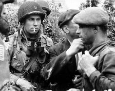 """Captain Kenneth L. Johnson and paratroopers of Hq & Hq Co. S-2 Intelligence Section, 508th PIR, 82nd Airborne Division """"All Americans"""", talking with two Francs-tireurs partisans in the village of Saint Marcouf, Normandy, France. 6 June 1944."""
