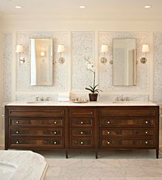 Thanks to McGill Design Group. I love the richness of the wood! Gorgeous, chic bathroom design with marble floor tiles, wallpapered panels, chrome sconces, chrome fixtures, silver mirrors, double sink antique vanity with marble counter tops. ivory cream white gray brown bathroom colors.