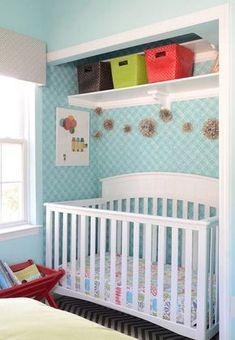 Nursery with white crib in closet covered in white and turquoise geometric wallpaper below colorful framed art and a gold pom pom garland under white shelves lined with brown, green and red woven baskets. House Of Turquoise, Crib In Closet, Decorating Your Home, Diy Home Decor, Nursery Design, Organizing Your Home, Home Crafts, Cribs, Diy Furniture