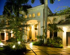 A custom designed lighted night view of a beautiful home in Boca Raton, Florida. Driveway is made of coral tiles.