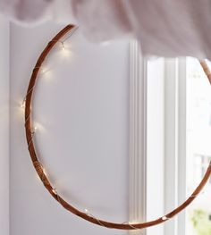 A wooden hoop is wound with a string of lights.