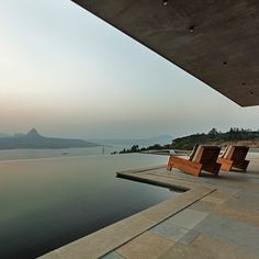 Volcanic stone walls and sculptural skylights are among the features of this holiday home by Khosla Associates, which looks out over a picturesque mountain lake in southwest India.