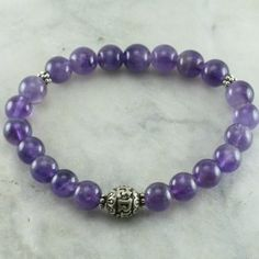 """The Wisdom Ayurvedic Bracelet is made from 21 amethyst mala beads. It is completed with a Sanskrit """"OM Mani Padme Hum"""" mantra bead. Mala beads for pitta."""