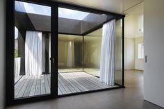 Vor und hinter der Glasfassade laufende Vorhänge verwischen die scharfen Konturen der Architektur.   btob architects © Roger Frei