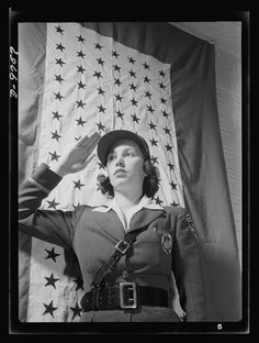 Safe clothes for women war workers. Estelle Hendel, twenty-eight, a guard at the Bendix Aviation Plant in Brooklyn, stands before the company service flag and gives the correct salute. Bendix Aviation Plant, Brooklyn, New York Photographer Ann Rosener Created March 1943