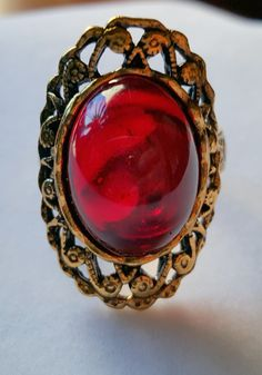 Inspired by the family Ruby Red Ring in Crimson Peak, this is a 18x13 mm cabochon with filigree brass and gold tone accents. It is an