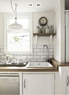 wooden counter, tiles, simple white cupboard door, stainless appliances, wood shelf, ceramic sink. all lovely