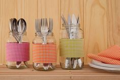Esta ideia é bem simples: após a limpeza do vidro, tudo o que você precisa fazer é envolver o recipiente com tiras de tecido xadrez de algodão e grudá-las com cola pano. Cada um dos vidros armazena um tipo de talher.