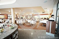 Interior of spacious modern hotel restaurant with counter in foreground.