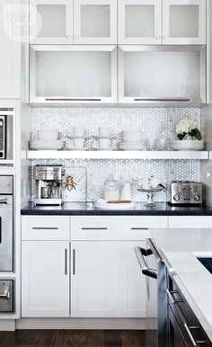 Such a cute kitchen and a great way to run stock cabinets to the ceiling and a shelf under rather than hanging them with that cheap, awkward empty space above!