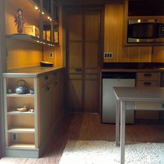 Chris and Melanie Heininge's tiny house kitchen has a built-in GE microwave, GE glass stove top, Frigidaire 5 cubic foot fridge, 22-inch Hitachi flat-screen TV and custom cabinets. (Photo by Chris and Melanie Heininge)