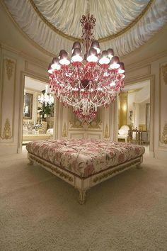 Boudoir if this was mine i dont think i would ever leave my house everything about it is wonderful!!!! pink floral pattern of bed oversized chandalier gold trim cream walls white furnature