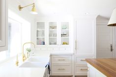 White kitchen with wood countertop on island and gold overhead wall sconce