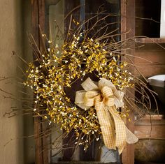 """This 24"""" in diameter spring wreath features yellow and cream pip berries. It is topped off with a burlap and yellow gingham bow."""