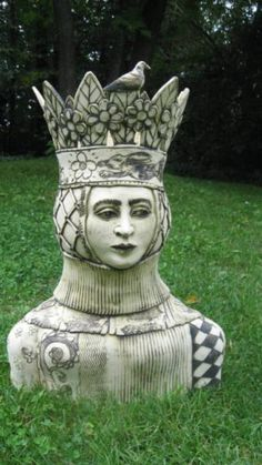 Garden statue of head and shoulders of queen with crown who looks like a queen seen on a normal deck of playing cards by Chandler Swain
