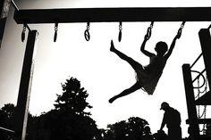 girl on swinging on climbing bar shilouette