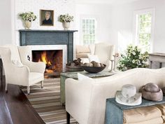 """Then she filled the house with furnishings in her trademark white palette, enriched with soft grays that seemed to suit the New England locale. """"This house is much simpler than my previous homes,"""" says Nancy. """"As you gain experience, you realize less is really more."""" In the living room, the furniture is covered in homespun linen. """"It lets you easily change the look with pillows and rugs,"""" says Nancy. She also took out the raised paneling, painted the brick fireplace white, and added an…"""