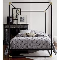 "frame canopy bed | CB2 posh retreat. Matte black powdercoated iron streamlines the classic canopy bed in dramatic silhouette. Edged with iron corners finished in glam plated brass, dark design rises 80"" high from the ground. Designed by Ceci Thompson to ""create a natural focal point in the room,"" box frame floats on airy, space-defining base. Shines with simple bedding."