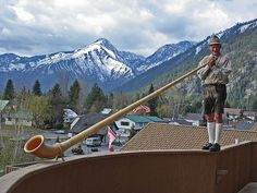 The alp horn player at the Enzian Inn in the town of Leavenworth, WA. He plays every morning on this balcony, 4-stories above ground level. Some of the Cascade Mountain foothills are in the background.