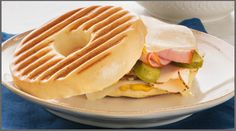 Makes 1 sandwich  Ingredients:   1 Village Hearth Plain Bagel  2 slices Swiss cheese  2 teaspoons yellow mustard  2 slices deli smoked turkey breast  2 slices deli Virginia ham  2 dill pickle planks   Directions:  Split bagel and spread mustard on each side. Top one half with 1 c