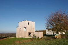 """Bernard Quirot Architecte & Associes has designed the """"Sampans House,"""" a beautiful three-storey residence that captures the engaging views of the lush landscape surrounding it in Jura, France. It rests on a small hill in its boxy form emphasizing itself as a vertical and compact structure. The home is encased with a natural Douglas pin …"""