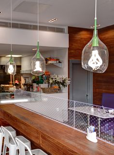 A good look for Plumen: accessorized with a Decode Vessel Shade and casually lined up above a counter in the fast food restaurant Roosters Piri Piri.