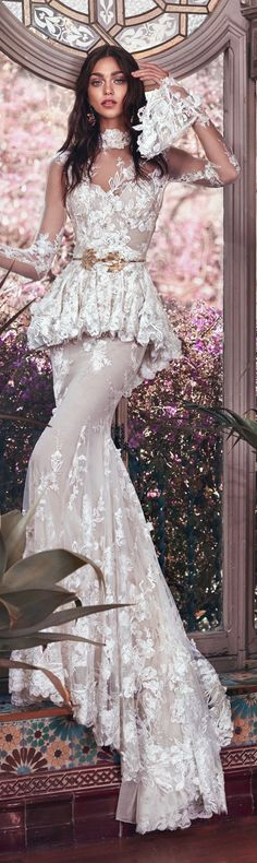 A Victorian sheer gown with 3D floral embroidery and a high neckline and sleeves. The gown has a peplum with an impressive detachable train.