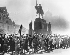 9th May 1945: A crowd of Czechoslovakians marching past a statue and war-damaged buildings in Prague, Czechoslovakia, to celebrate victory over the Germans. (Photo by Keystone/Getty Images)