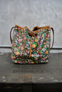 Kenzo floral bucket bag  1980s  Kenzo PARI$  adorable black leather floral printed bucket bag  tan leather trim, straps and drawstring closure