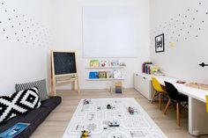 ואחרי. בעתיד זה יהיה חדרה של התינוקת שבבטן, כרגע הוא עוצב כחדר משחקים לשני הגדולים יותר. על הקירות הלבנים הודבקו מדבקות שחורות בצורת + ובין פינת העבודה למזרון הרביצה הונח שטיח לינוליאום לבן עם איורים, בעיצוב Petek design. את הצבעים מוסיפים לחדר הצעצועים והספרים (צילום: שירן כרמל)