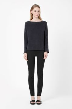 Simple and versatile, this long-sleeved top is made from pure silk with a soft, chalky quality. A loose, relaxed fit designed to drape on the body, it has a wide round neckline, centre seam detail and curved graduated hem.
