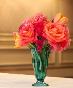 An Indian wedding centerpiece at, The Ritz Carlton in the Mercier Terrace room. A short arrangement, using orange roses, orange tulips, hot pink celosia (coxcomb), hot pink roses, and pink/orange dahlias, in a turquoise soda shop vase.
