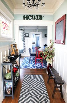 """As soon as you step inside, you just know this is no average home. The entryway pops with eclectic details, from the chandelier to the """"Howdy"""" sign to the patterned rugs. She would hate to have a """"matchy matchy"""" home, she says, because color, texture, and pattern are what add personality to a space."""