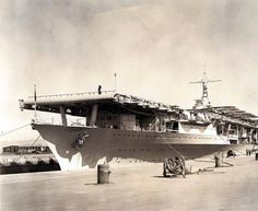 """USS Ranger (CV-4) entering Hunter's Point Drydock, San Francisco, California, 2 March 1937. Note .50 Cal. AA Machine-Guns (uncovered) along the Flight Deck, forward. Note also 5"""" Guns and Saluting Guns at teh Bow (Port and Stbd). She was the first carrier to be docked with planes on board. NHHC Photograph Collection, NH 51826."""