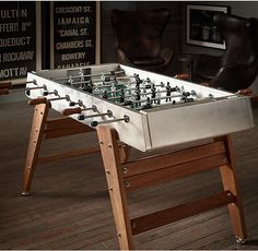 RH's Competition Foosball Table:Americans call it Foosball. The French call it Baby-Foot. And in Spain, where this deluxe game table is made, they call it Futbolin. Enduringly built of stainless steel and durable iroko wood, our table promises to become a family favorite for years to come. Its handsome design and minimalist palette lend it uncommon sophistication, while its electropolished steel top makes it rugged enough for outdoor use.