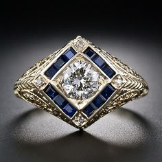 This unusual and distinctive original Art Deco diamond ring from the 1930s is crafted in bright 14 karat yellow gold (which is what makes it comparatively rare) and features a bright and lively (although highly included) .80 carat transitional-cut diamond framed in deep blue, calibre-cut sapphires and a tiny diamond at each point of the square setting. The mounting is elaborately ornamented with openwork and hand-engraving.
