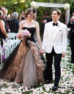 A black and champagne glamorous wedding dress for the bride and a white tuxedo with a black bow tie and black pants for the groom at a non-traditional wedding.