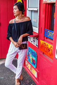 Nicole Warne of Gary Pepper Girl wears a navy off-the-shoulder top, striped trousers, slide sandals, and a Charlotte Olympia bag