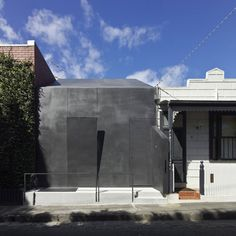 A drawbridge-like flap lowers from the steel-plated facade of this Melbourne bunker to reveal a bedroom window. Australian architects Muir Mendes designed Law Street House for themselves. The building occupies the site of a former workman's cottage and is flanked on three sides by other houses. Designed to be termite-proof, the house features a steel