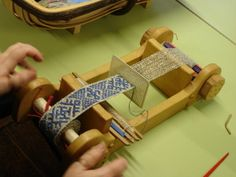At an SCA event a couple of weekends ago, a lady was working on a really wonderful small loom: She was making this fantastic brocade-type trim, weaving a straight tabby with an overshot pattern. The results were fantastic, and small...