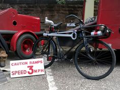 This curious velocipede is an ex-London Fire Brigade hose layer bike.  The vehicle in the background is a 1960s-era hose layer, a specialised fire appliance that carried huge quantities of hoses internally to connect distant fire hydrants or other water sources to the scene of a fire. It carried a trailer pump to assist in moving the water along. Such a vehicle would be dispatched to support a major emergency where local water supplies may be insufficient to fight the fire. Such was the…