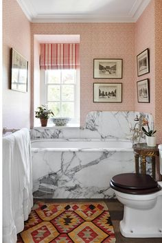 Interior designer Amanda Hornby has used 'Vermicule' wallpaper from Pierre Frey in the bathroom, which contrasts with the marble bath surround and swooping curved splashback, sourced from a quarry that was reopened 20 years ago when the marble in the Hall of Mirrors at Versailles was being restored, 'I love its funky psychedelic orange and red veins,' says Amanda.    Taken from the August 2015 issue of House & Garden.