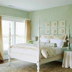 Pretty as a seaside scene. Sand-color drapes & bedding & pale seafoam-green walls evoke the misty moods of the ocean. A slightly distressed four-poster channels an old-fashioned beach house.
