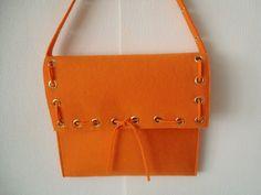 orangefarbene Filztasche mit goldfarbenen Ösen gestanzt. Eine originelle Tasche in einer der modischsten Farben der Saison.